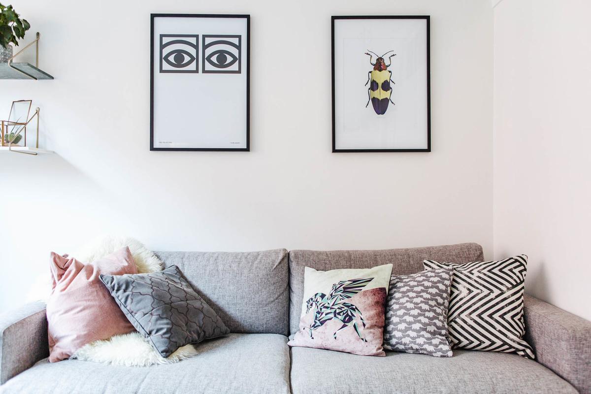 Картины над диваном оживляют большую белую стену.