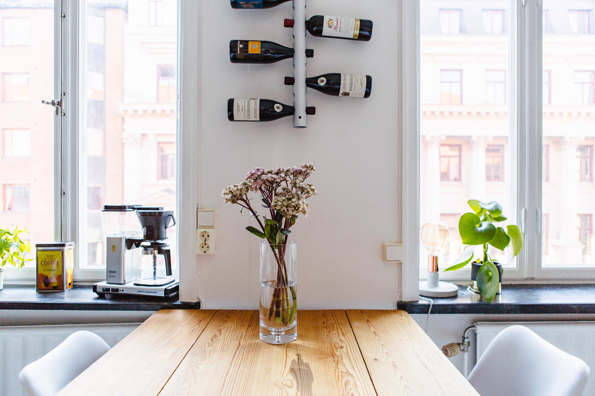 Креативный держатель для винных бутылок над обеденным столом и кофеварка на подоконнике экономят место на столе.