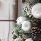 При ближайшем рассмотрении можно видеть что елка украшена достаточно простыми и скромными елочными игрушками.