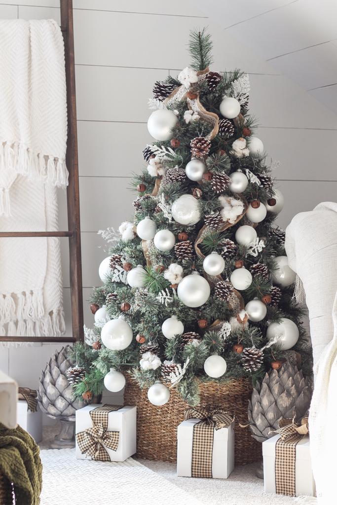 Елка расположенная в углу комнаты богато украшена серебристыми матовыми и глянцевыми шарами, настоящими шишками и орешками-колокольчиками. Важной частью декора являются и подарочные коробки с бантиками небрежно валяющиеся у елки.