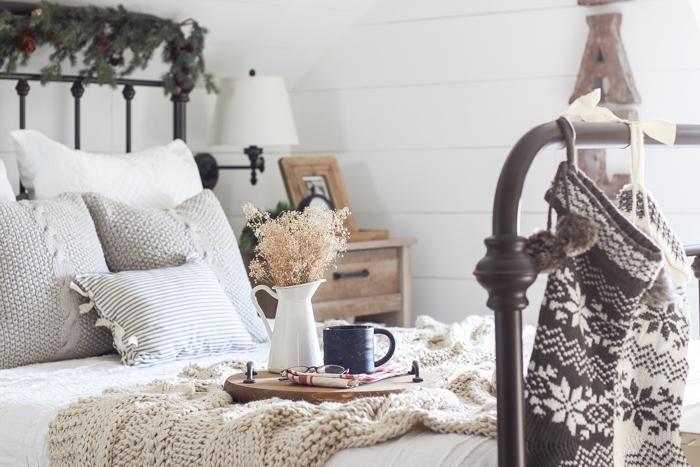 Круглый деревянный поднос отлично вписывается в рустикальный интерьер спальни.