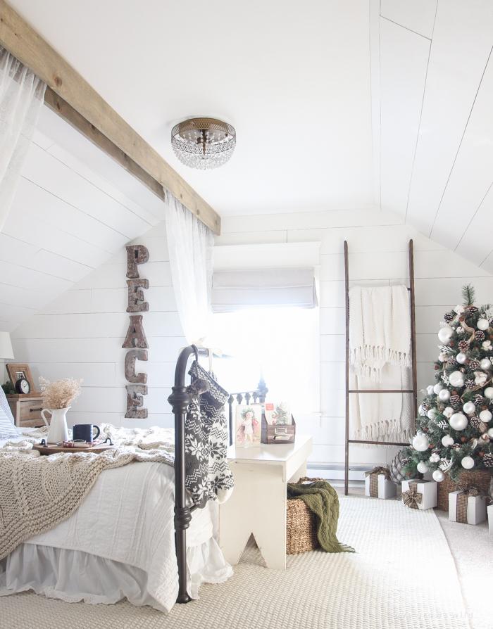 Спальня подготовленная к новому году оформлена в светлых и натуральных тонах.