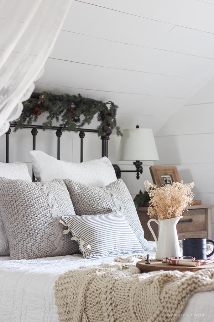 Удивительно смотрится хвойная гирлянда в изголовье кровати, не лишая ни одного уголка спальни праздничной атмосферы.