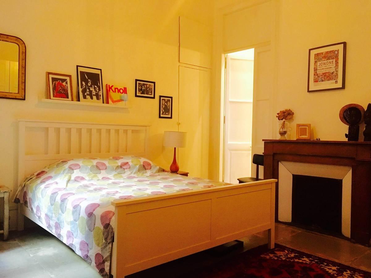 Небольшая спальня с камином и высокими потолками, как во всей квартире.