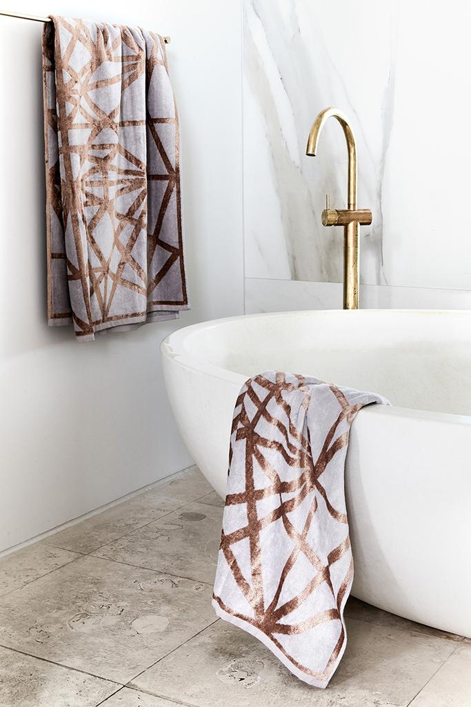 Отдельно стоящая белая ванна с латунным краном