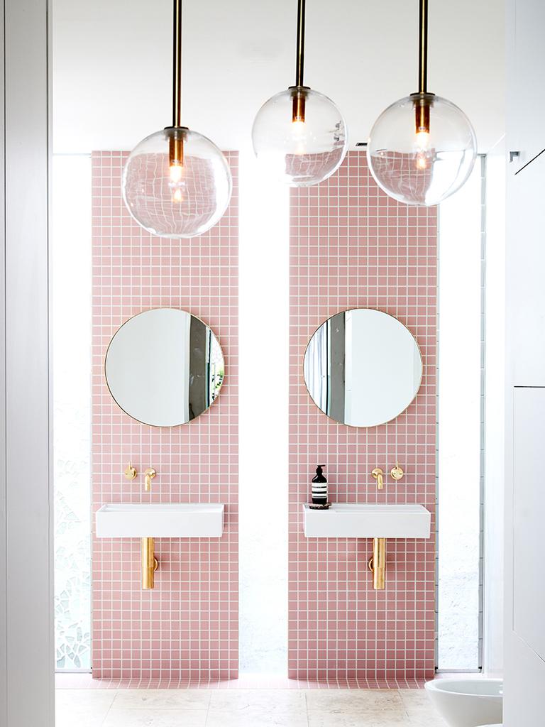 Узкие вертикальные окна ярко освещают ванную комнату в дневное время.