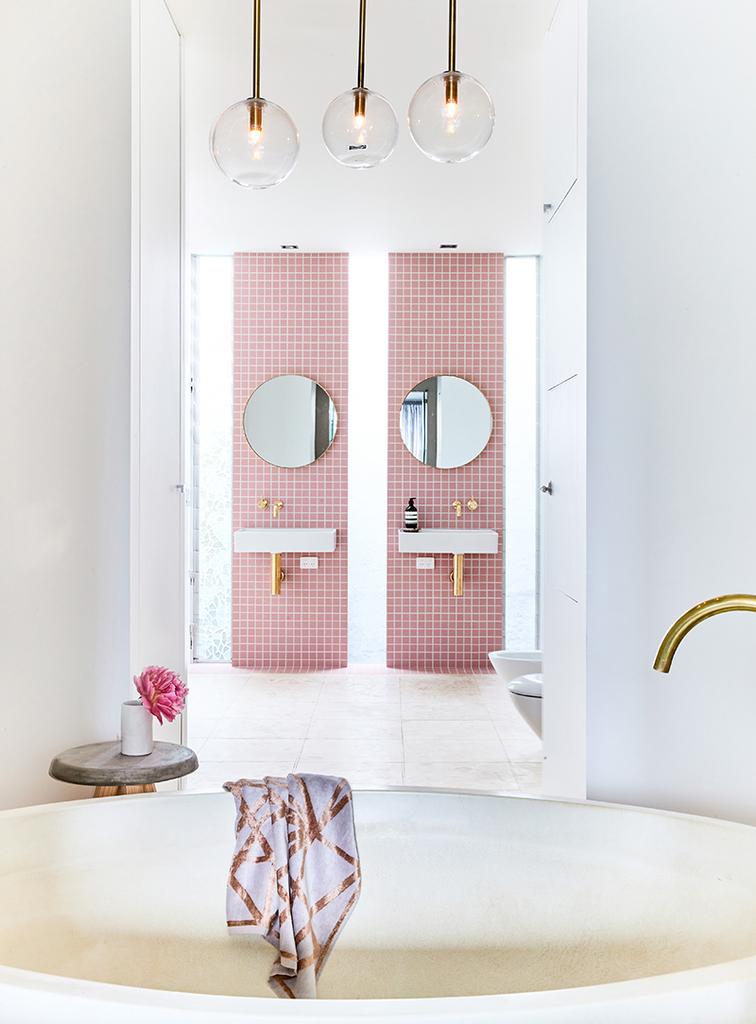 Вертикальные розовые полосы в ванной комнате возле умывальников и душа совершенно меняют восприятие интерьера. Холодный интерьер вдруг становится теплым, уютным и гостеприимным.