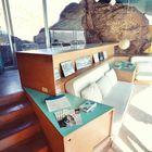Еще один вид на гостинную. Видна встроенная мебель и стол над диваном. (гостинная,столовая,жилая комната,1950-70е,минимализм,архитектура,дизайн,интерьер,экстерьер,мебель,маленький дом)