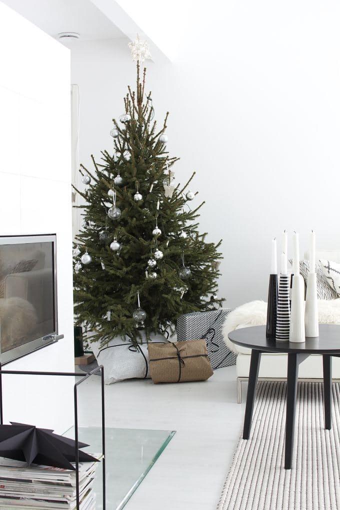 Что может быть романтичнее елки у камина скромно украшенной прозрачными и серебряными шарами. Такая елка идиально подходит к этому минималистскому черно-белому скандинавскому интерьеру