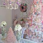 Белая елка с пастельными украшениями и розовой мишурой.