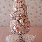 Небольшая настольная елочка украшенная ювелирными украшениями и бантиками.