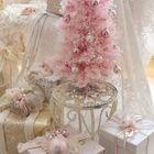 Розовая елочка украшенная золотистыми шариками. Елка окружена подарками в соответствующим образом декорированных коробках.