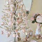 Уникальная настольная елка украшенная белыми бусинками и розовыми елочными игрушками.