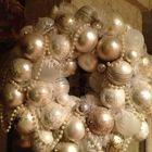 Венок из серебристых шаров и шаров цвета слоновой кости украшенный жемчугом.