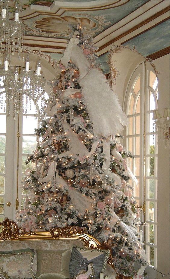 Большая новогодняя елка украшенная белыми и розовыми украшениями, искусственным мехом и гирляндой.