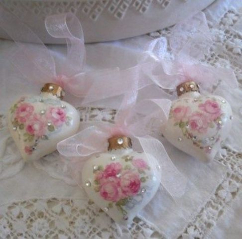 Елочные украшения в виде сердечек с розовыми ленточками с цветочными орнаментами.