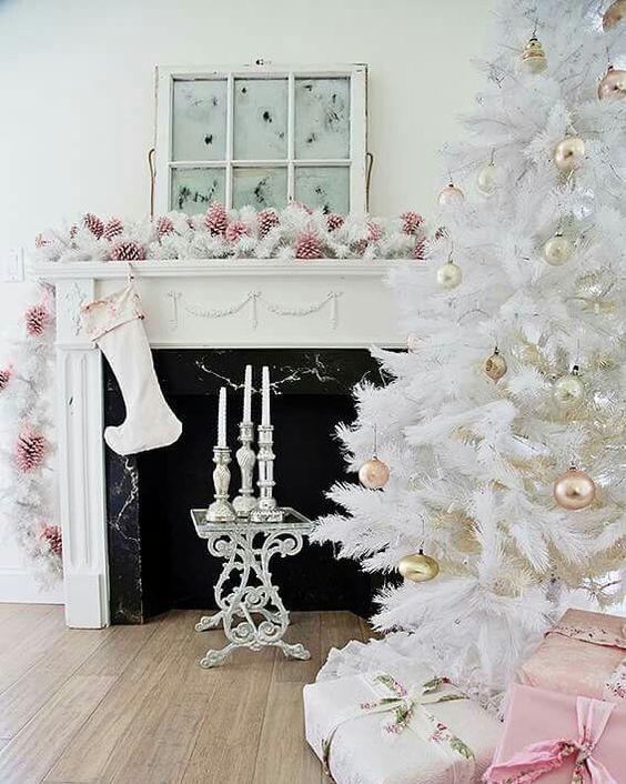Гостиная в стиле шеби шик с белой елкой украшенной золотыми шарами. Камин украшают розовые шишки.