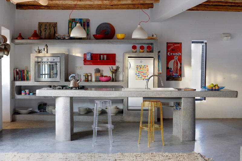 Бетонная кухня выглядит современно и традиционно одновременно. Кухонный остров, столешница и полки выполнены из бетона. Традиционности интерьеру придают и открытые деревянные балки
