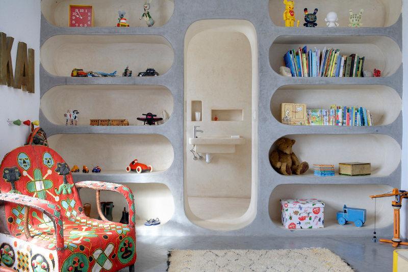 На этой стене можно видеть всю прелесть глинобитной архитектуры. Полки сделаны встроенными в стену и выполнены из глины. Дверной проем без двери ведет ванну. Традиционные приемы строительства выглядят очень современно.