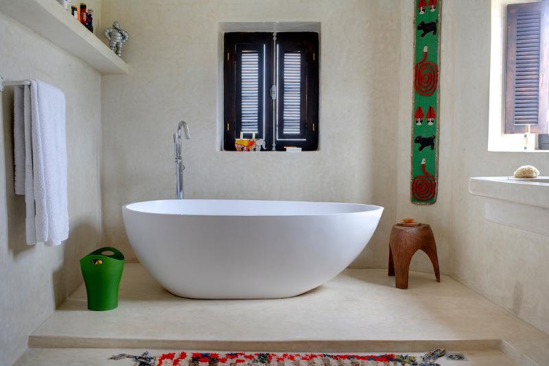 Просторная ванная комната с отдельно стоящей ванной. На окнах установлены распашные деревянные жалюзи