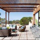 Своеобразная летняя гостиная на террасе под тростниковой крышей с плетеной мебелью.