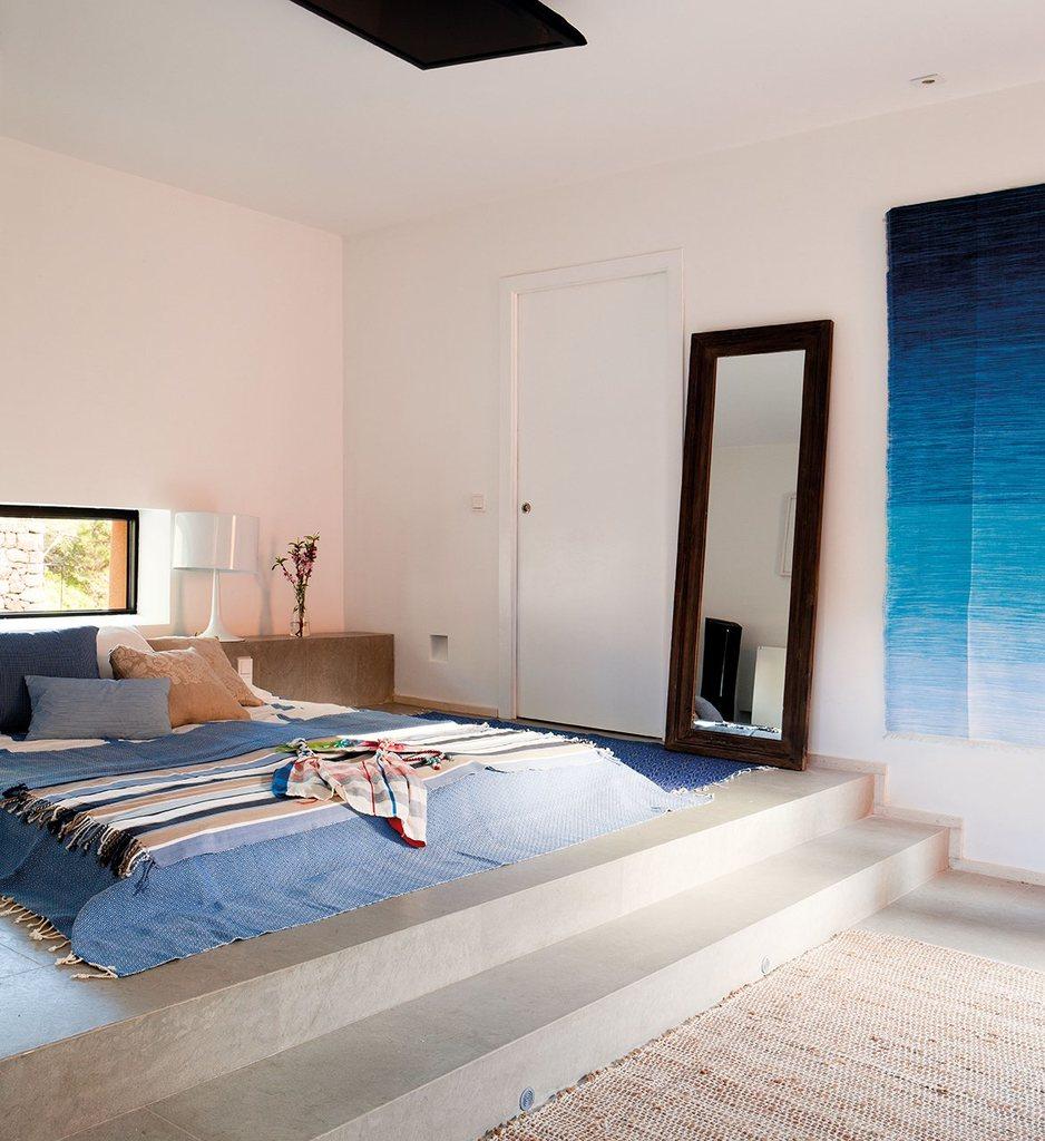 Матрац в спальне лежит прямо на полу на небольшом бетонном подиуме.