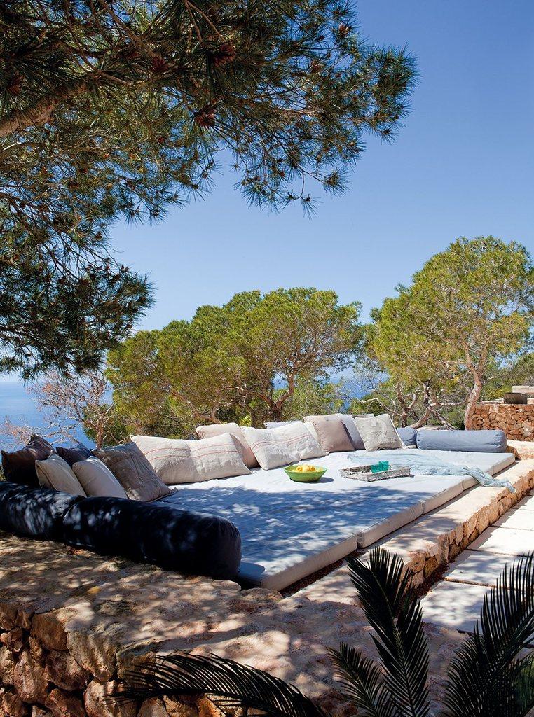 Место отдыха на террасе с мягкими матрацами и подушками, лежа на которых можно позагорать и насладиться местными фруктами.