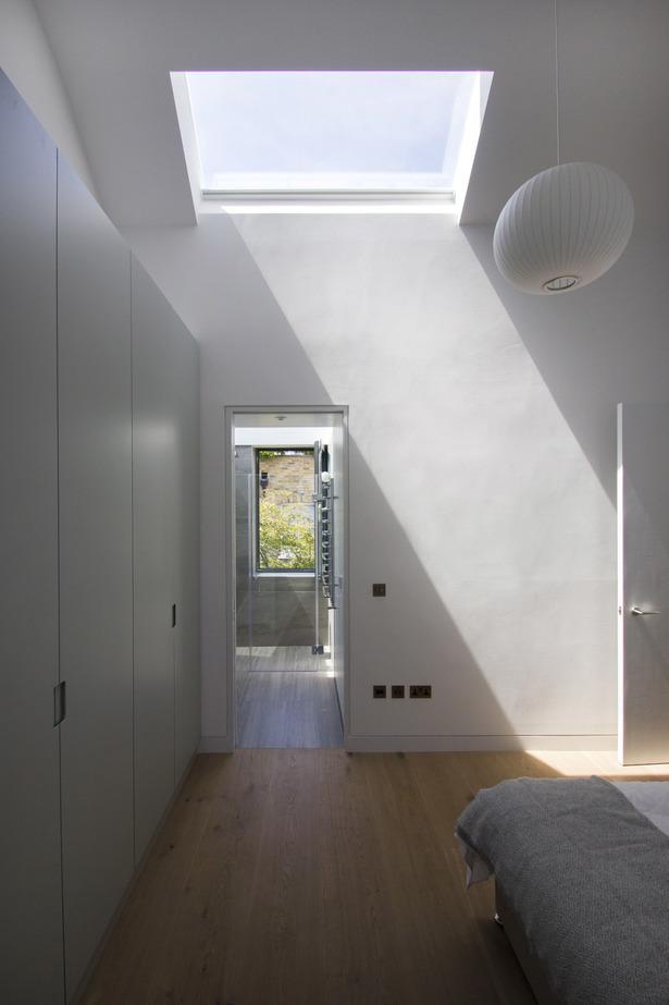 Гостевая спальня в подвале освещается светом через окно в полу первого этажа.