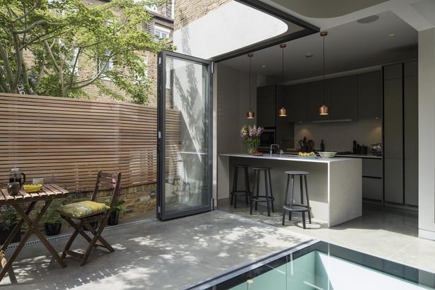 Когда стеклянные двери гостиной-кухни открыты, то бетонная барная стойка становится еще интереснее и функциональнее