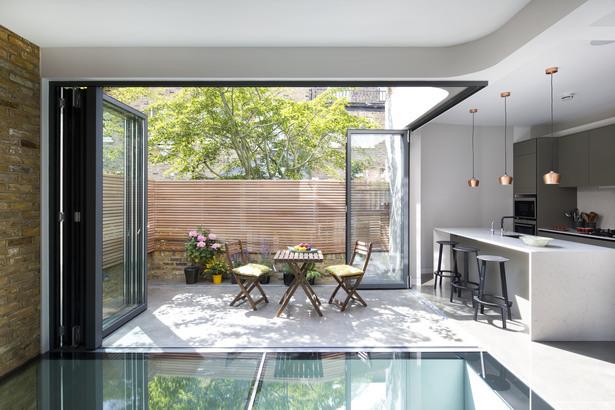 С открытыми окнами первого этажа бетонная терраса становится частью жилого пространства.