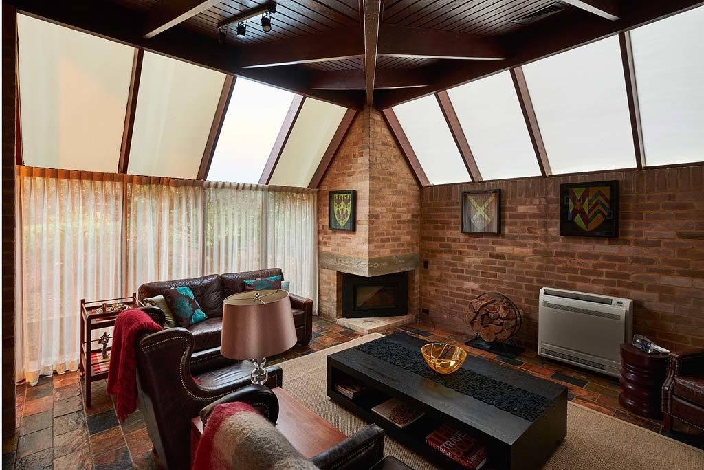 Семейная гостиная с камином и остекленной с двух сторон крышей.