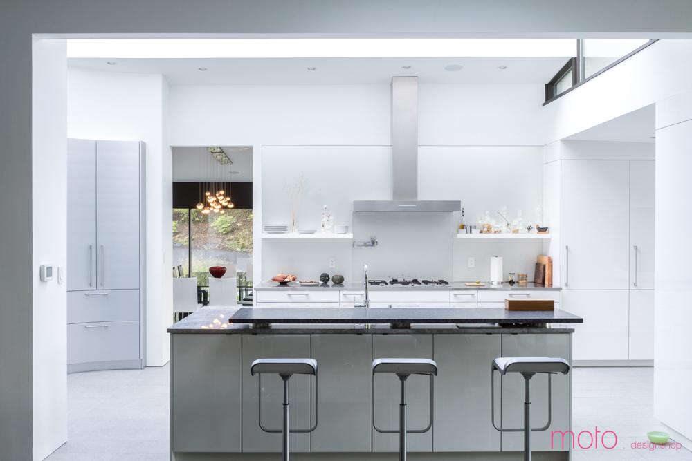 Кухня скрыта от столовой и остекленного переднего фасада стеной, а от гостиной отделена лишь кухонным островом с барной стойкой.
