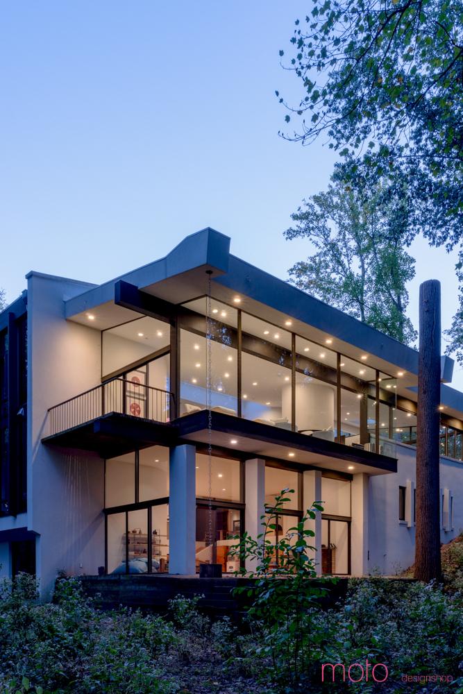 Поскольку дом находится на склоне, то со стороны склона дом имеет два этажа. Они полностью остеклены и имеют свои балконы и террасы.