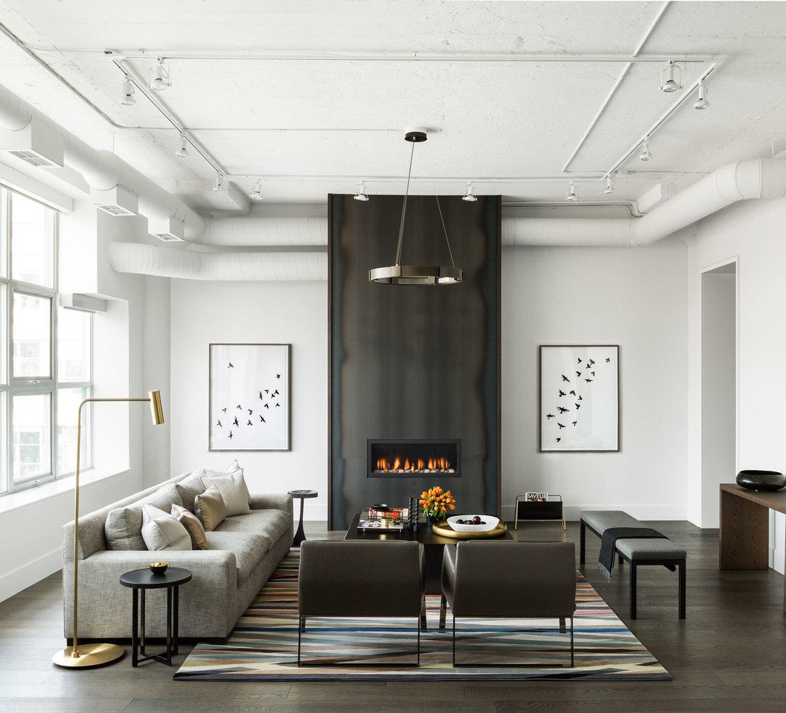Центром гостиной по праву можно считать стальной камин от пола до потолка из неокрашенной горячекатаной стали имеющей неоднородный цвет