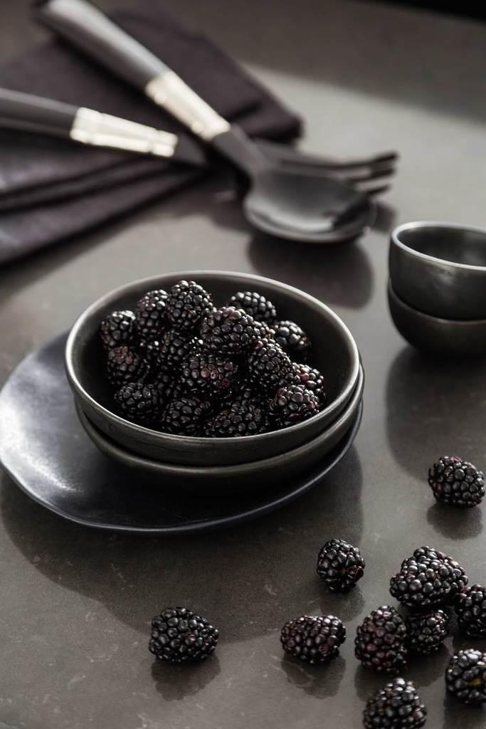 Черная посуда и столовые приборы на серой полированной бетонной столешнице обеденного стола.