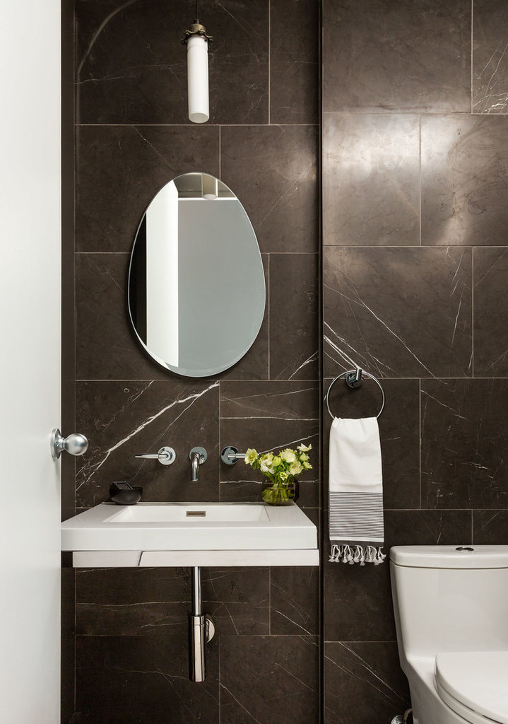Простая и просторная одна из ванн с облицованными мрамором стенами.