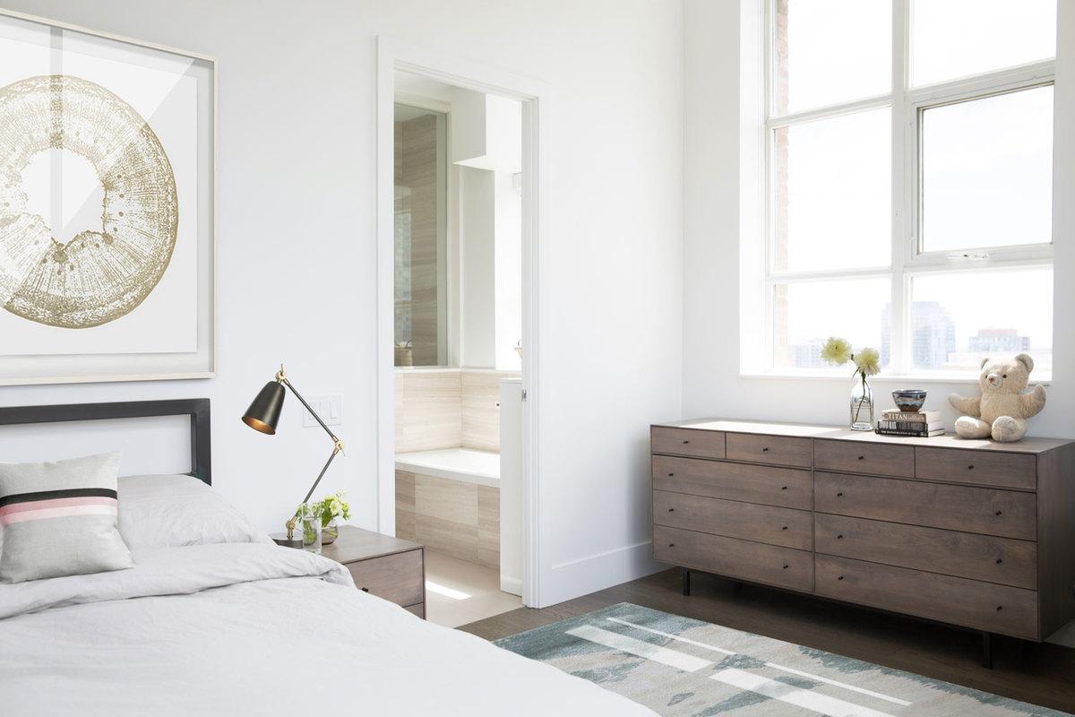 Спальня светлая, благодаря большому окну из которого открывается вид на окружающие городские пейзажи, с белыми стенами. Спинка кровати также как и плательный шкаф из неокрашенной стали