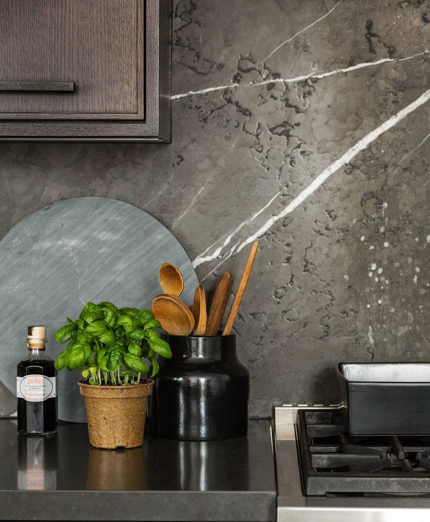 Стена рядом с рабочей областью кухни отделана серым мрамором с белыми прожилками, который имеет грубую текстуру.