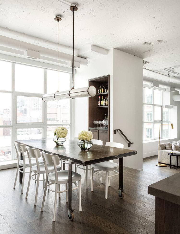 В центре столовой расположен уникальный выполненный на заказ стальной обеденный стол с бетонной столешницей.