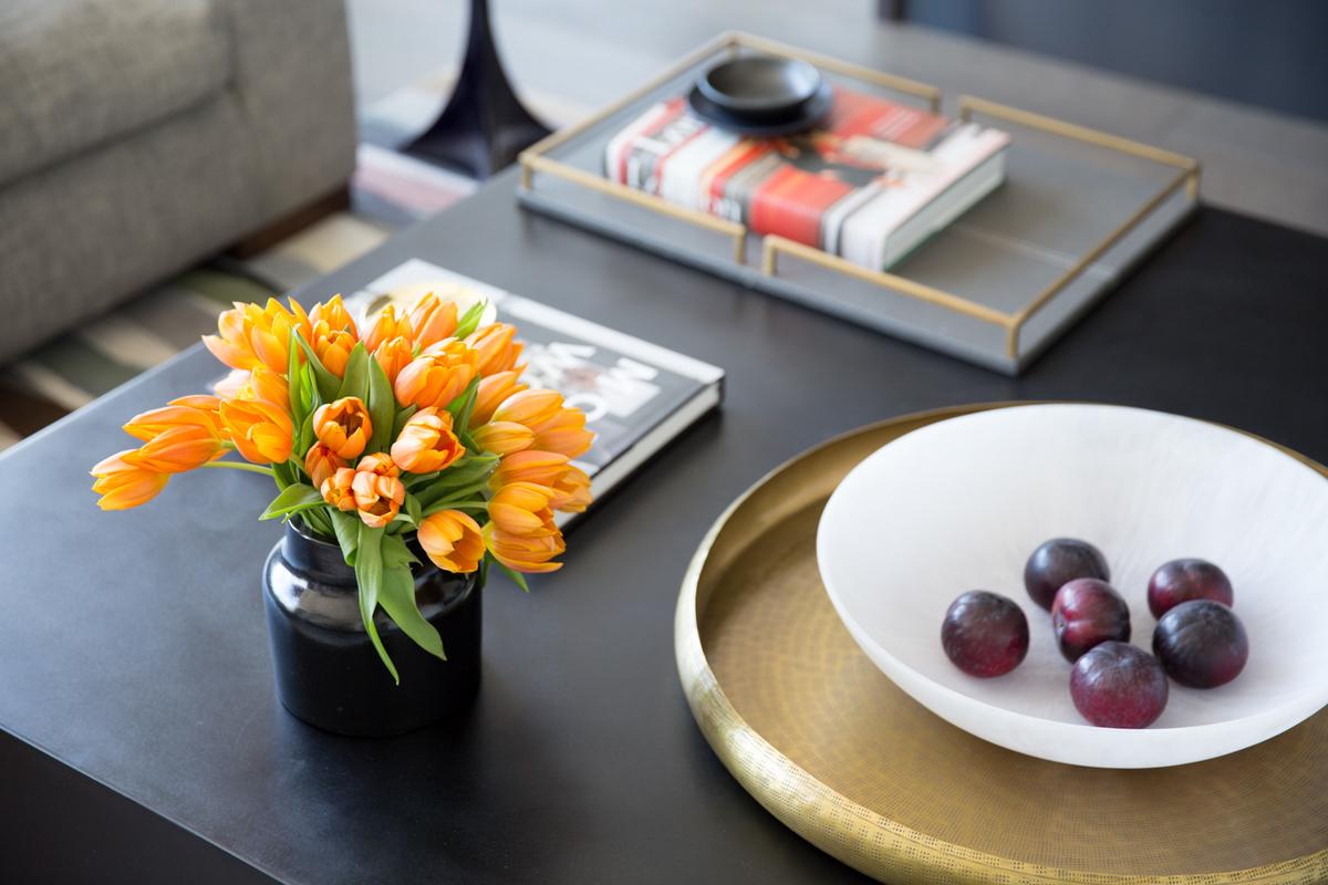 Желтая латунь выгодно смотрится на фоне черной столешницы журнального столика в гостиной.