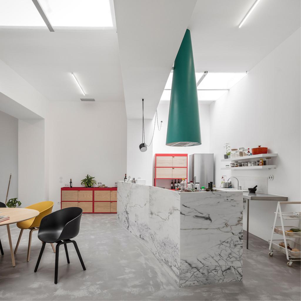 Кухонный остров отделанный мрамором выглядит несколько вызывающе в строгом индустриальном окружении