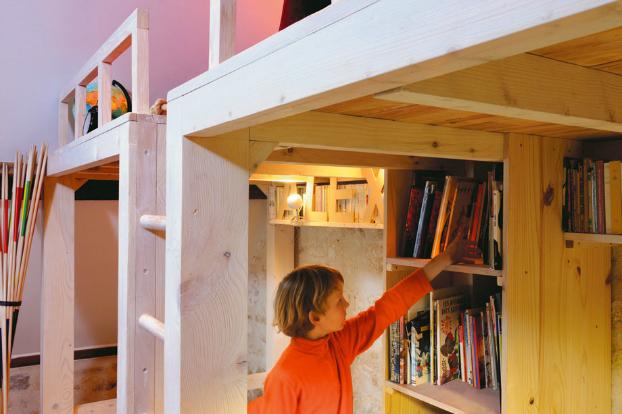 За лестницей от пола до потолка расположены емкие стеллажи для книг.