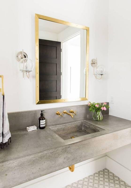 Серый массивный умывальник отлично сочетается с золотистыми кранами и прочими элементами.