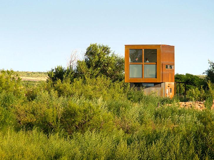 Большое окно в спальне второго єтажа с матовой нижней частью открывает вид на окружающий пустынный ландшафт.