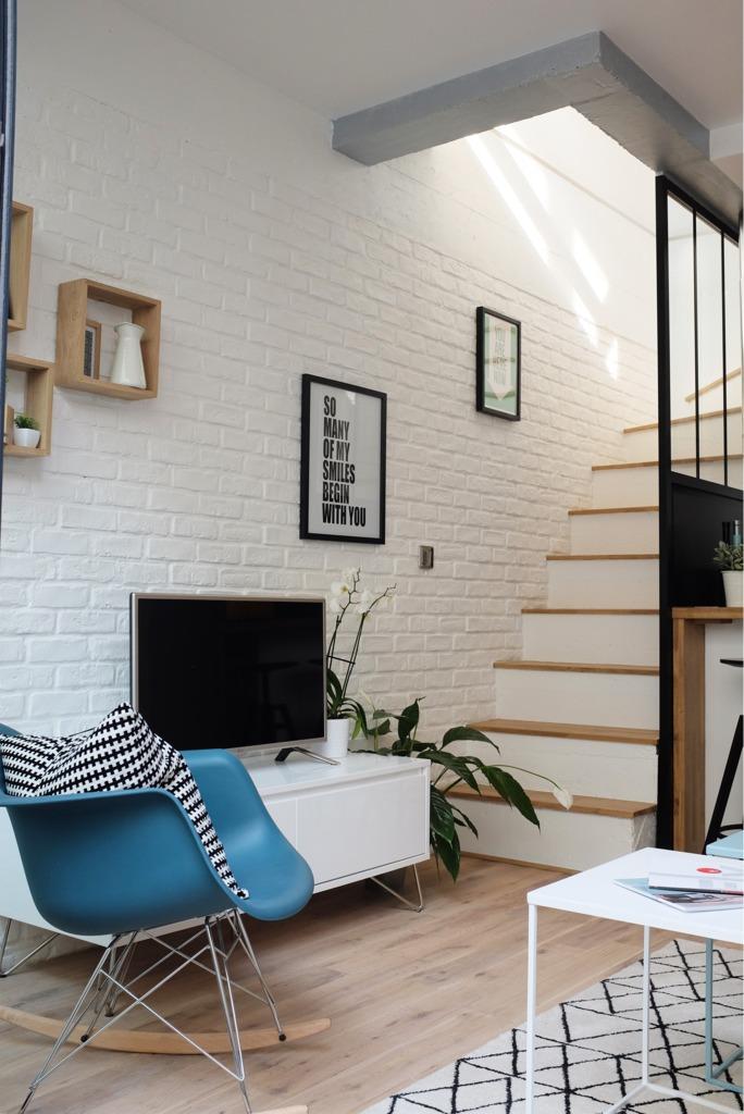 Стена отделанная под кирпич в гостиной и вдоль лестницы создает квартире модную ауру современного лофта.