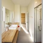Деревянная столешница добавляет тепла в холодный интерьер ванной комнаты. (современный,архитектура,дизайн,экстерьер,интерьер,дизайн интерьера,мебель,маленький дом,ванна,санузел,душ,туалет,дизайн ванной,интерьер ванной,сантехника,кафель)