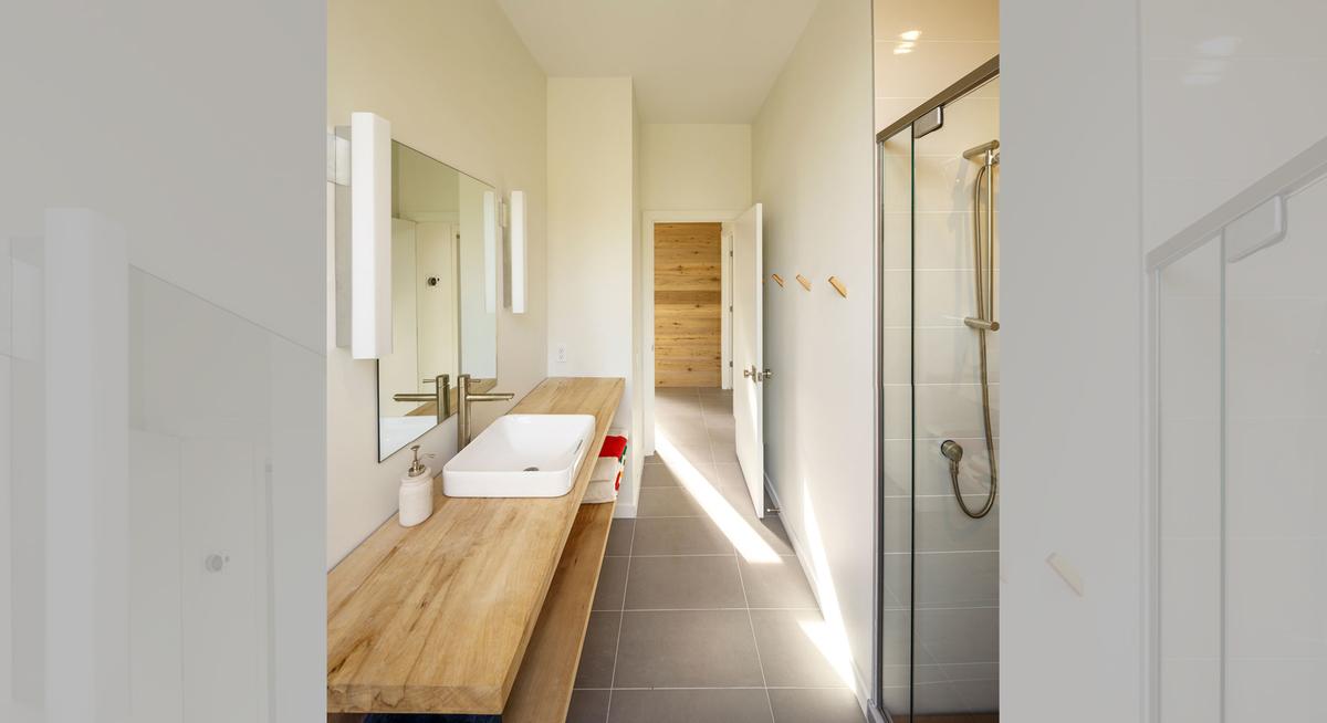 Деревянная столешница добавляет тепла в холодный интерьер ванной комнаты.