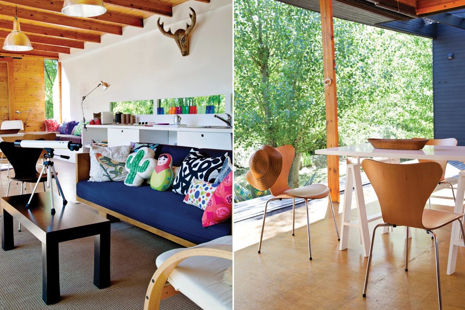 Диван в гостиной выполнен из массива дерева, стулья Якобсен из гнутой фанеры в столовой сочетаются с фанерным полом