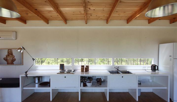 Кухня представляет из себя столешницу проходящую вдоль жилой комнаты. Под ней сделаны три открытых ниши и три закрывающиеся откидными дверцами
