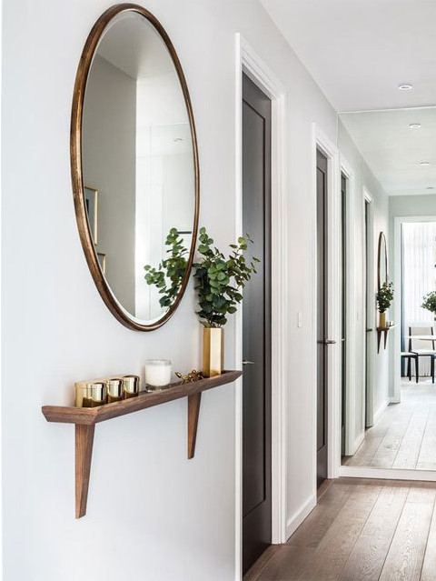 Элегантное зеркало с полочкой может самостоятельно создать интерьер прихожей. Стоит обратить внимание на зеркало во всю стену на дальней стене, оно визуально расширило пространство.